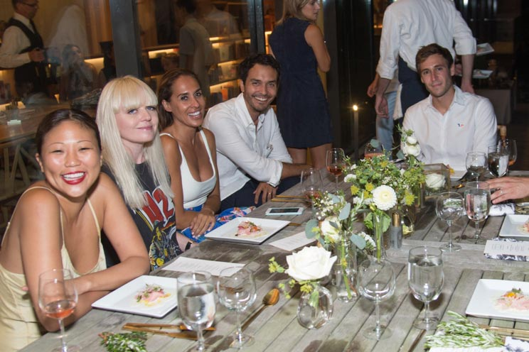 Photo of 5 smiling guests around a table about to enjoy a plated whitefish