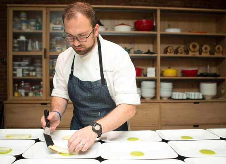 Photo of Chef David plating delicate cooked whitefish over small spots of pureed sauce