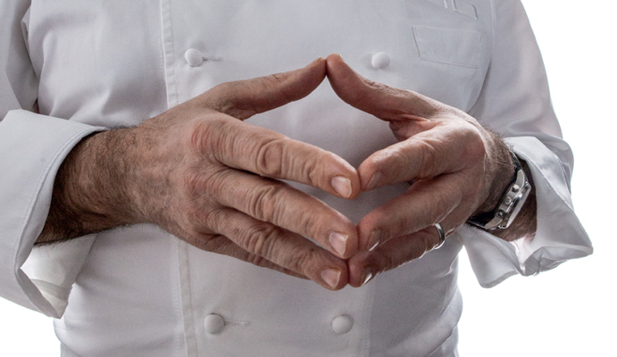 Close up of man's torso, wearing chef smock and with hands together, fingertips touching each other