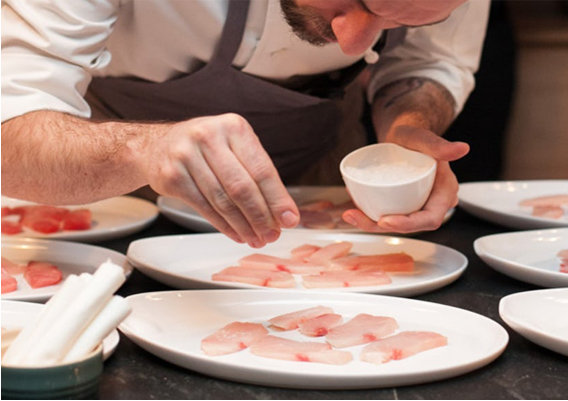 dineDK chef carefully sprinkling small amounts of salt on top of slices of a white fish