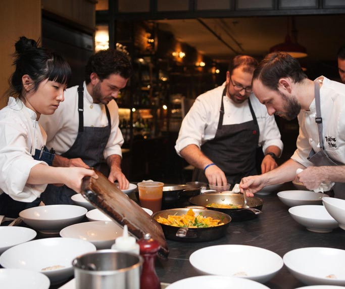 dineDK chefs plating around a sea of plates