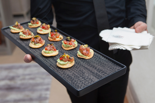 dineDK waiter serving canapes on a long black serving plate
