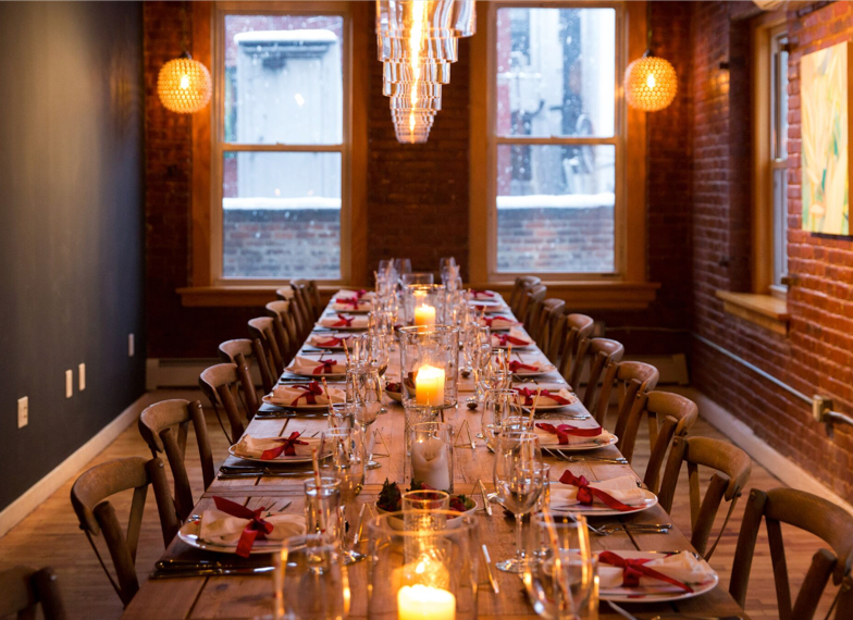 Long table that fits 20, with linen napkins wrapped with red ribbons. Warm lighting emitting from candles and two ball-shaped chandeliers. Brick walls on two sides of the room, with large windows, and a dark grey wall on the left side of the room.
